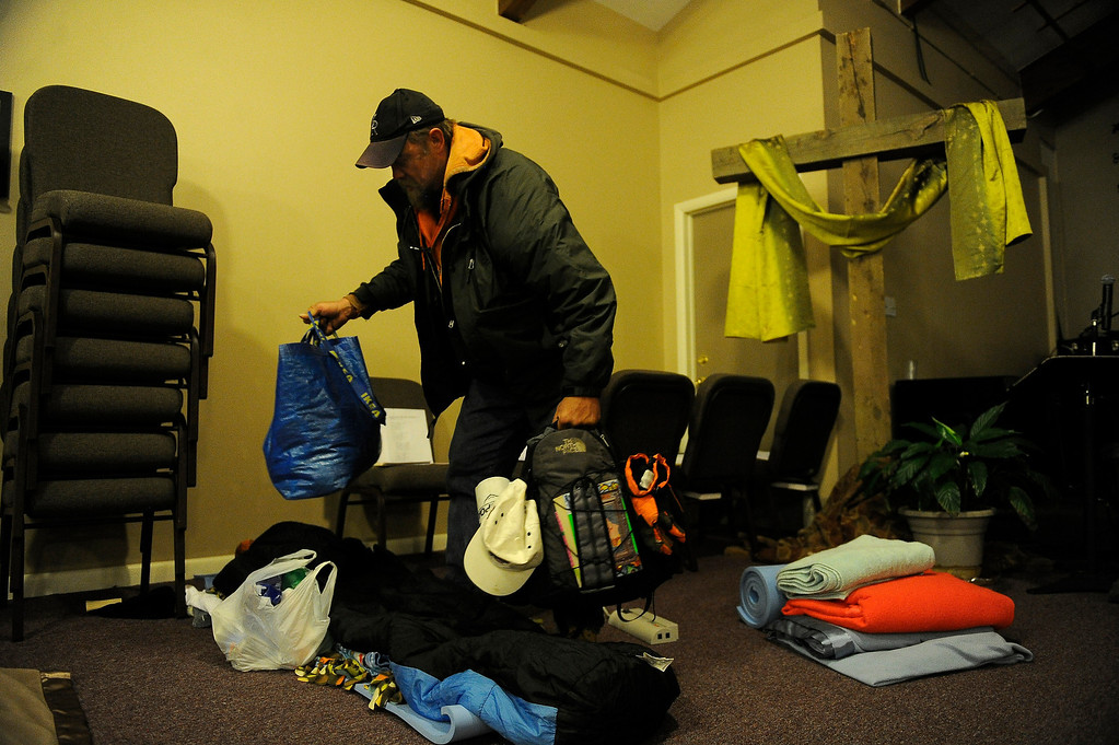 . GOLDEN, CO - JANUARY 22: Jerry Pierce sorts his belongings as he rolls out his bed roll and blankets while preparing to shelter overnight at Applewood Community Church in Golden, Colorado on January 22, 2014. The Jefferson County Action Center began partnering with churches last year to offer emergency shelter for the homeless on severe weather nights. (Photo by Seth McConnell/The Denver Post)