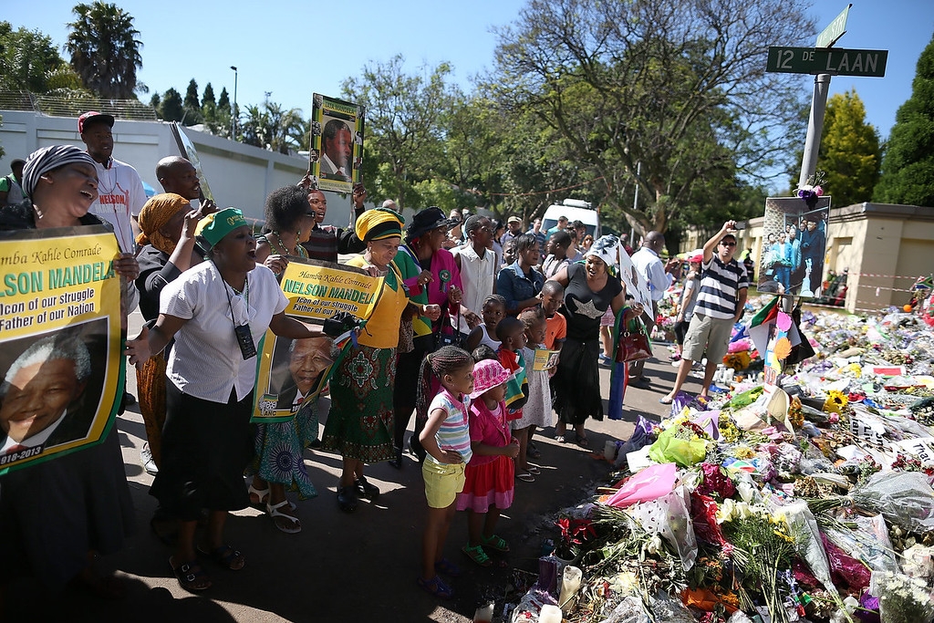 . Mourners gather outside the home of former South African President Nelson Mandela on the day that the iconic leader was laid to rest in his home village on December 15, 2013 in Johannesburg, South Africa.  Mr. Mandela passed away on the evening of December 5, 2013 at his home in Houghton at the age of 95. Mandela became South Africa\'s first black president in 1994 after spending 27 years in jail for his activism against apartheid in a racially-divided South Africa.  (Photo by Justin Sullivan/Getty Images)