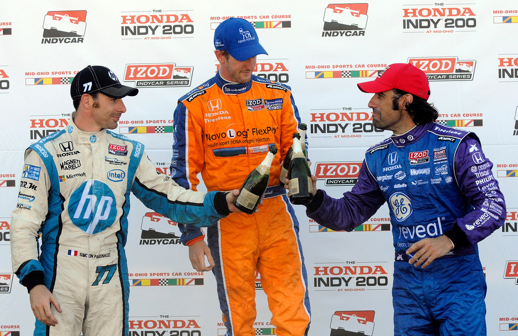 . Charlie Kimball, center, raises the first place trophy in victory circle after winning the Honda Indy 200 at Mid-Ohio Sports Car Course along with second place finisher Simon Pagenaud, of France, left, and third place finisher Dario Franchitti, of Scotland, in Lexington, OH Sunday, Aug. 4, 2013. (AP Photo/Tom E. Puskar)