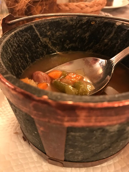 Soup in a rock and copper pail bowl