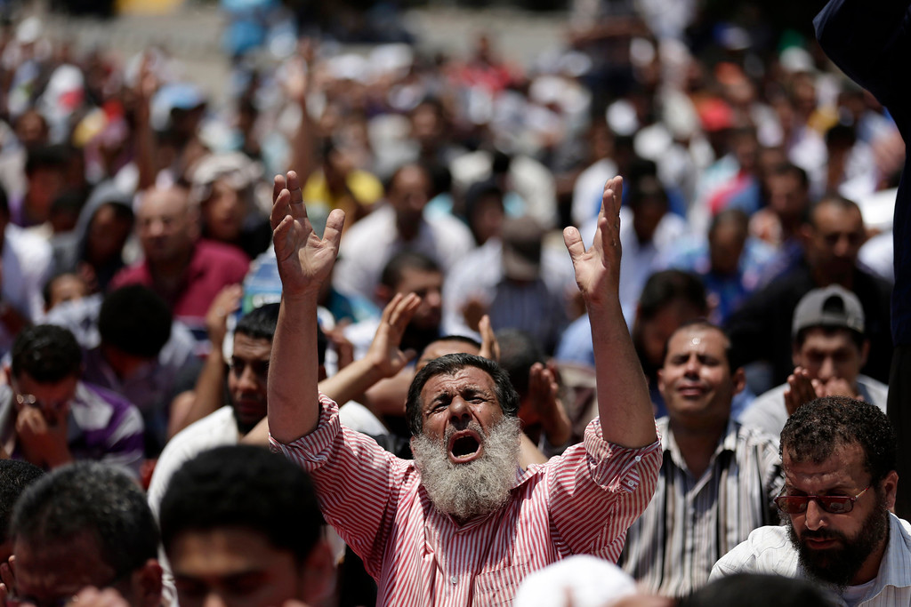 ". Supporters of ousted Egyptian President Mohammed Morsi pray during the Friday prayer before a protest near the University of Cairo, Giza, Egypt, Friday, July 5, 2013. Tens of thousands, mainly Islamists, chanted ""down with military rule\"" in protests around the country Friday, venting their fury at the military for ousting President Mohammed Morsi and vowing to restore him to office. The first major attack by militants, in Sinai, hiked fears that the Islamists\' extreme fringe will turn to violent retaliation for Morsi\'s ouster.(AP Photo/Hassan Ammar)"