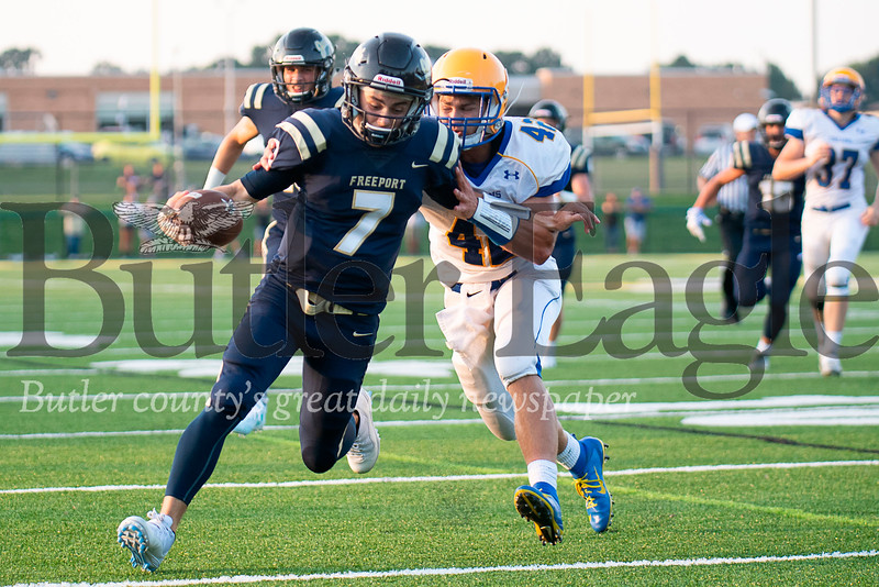 Freeport's Austin Romanchak (7) avoids the pursuit of Derry's Justin Flack (42) and takes a Patrick Keeley pass 26 yards for the opening touchdown of the game during the first quarter on Friday, Aug. 31, 2018 at Freeport Area Athletic Stadium.