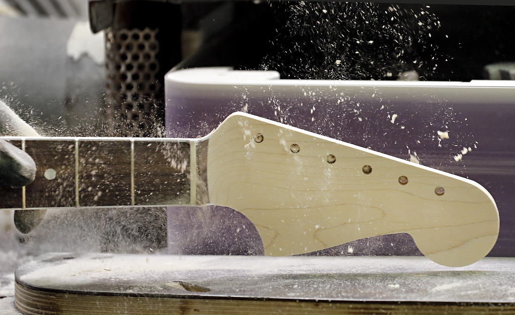 . A Fender Stratocaster electric guitar head stock is sanded at the Fender factory in Corona, Calif. on Tuesday, Oct. 15, 2013. The instrument, used by countless professional and amateur musicians, celebrates its 60th anniversary in 2014. (AP Photo/Matt York)