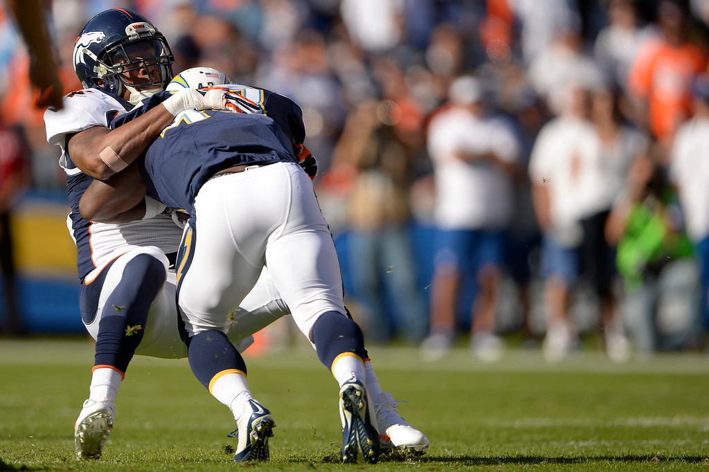 . SAN DIEGO, CA. December 14, - Outside linebacker Brandon Marshall #54 of the Denver Broncos is run over by running back Branden Oliver #43 during a tackle in the first half at Qualcomm Stadium December 14, 2014 San Diego, CA (Photo By Joe Amon/The Denver Post)