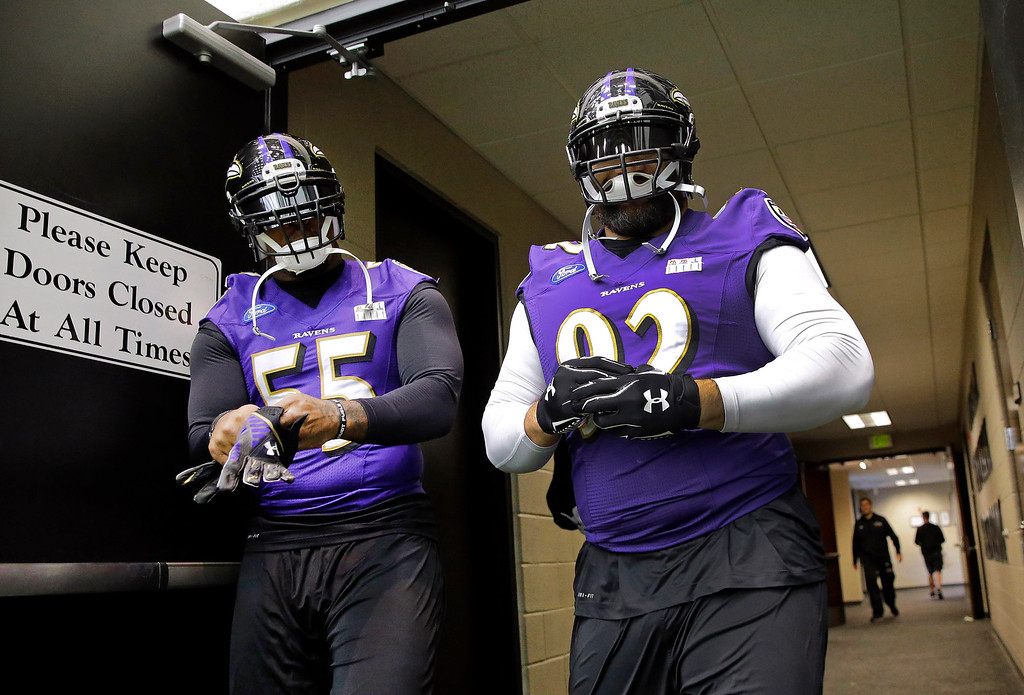 . Baltimore Ravens outside linebacker Terrell Suggs, left, and defensive end Haloti Ngata walk to NFL football practice, Tuesday, Dec. 30, 2014, in Owings Mills, Md. Ngata and the Ravens can only hope that a four-week suspension won\'t hinder his effectiveness in Saturday night\'s playoff game against the Pittsburgh Steelers. (AP Photo/Patrick Semansky)