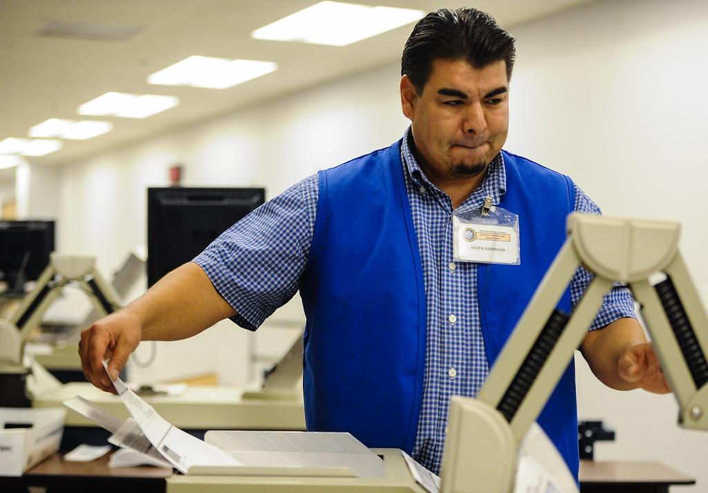 . Ballot counting team employee Javier Espinoza runs mail-in ballets through the counting process at the Registrar of Voters office in San Bernardino on Monday, Nov. 4, 2013. (Photo by Rachel Luna / San Bernardino Sun)