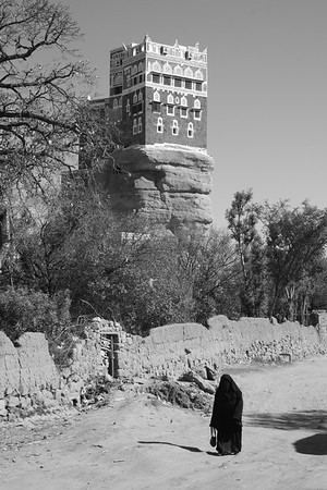 A woman walks past Imam Yahya's palace in Dar al-Hajar, Yemen