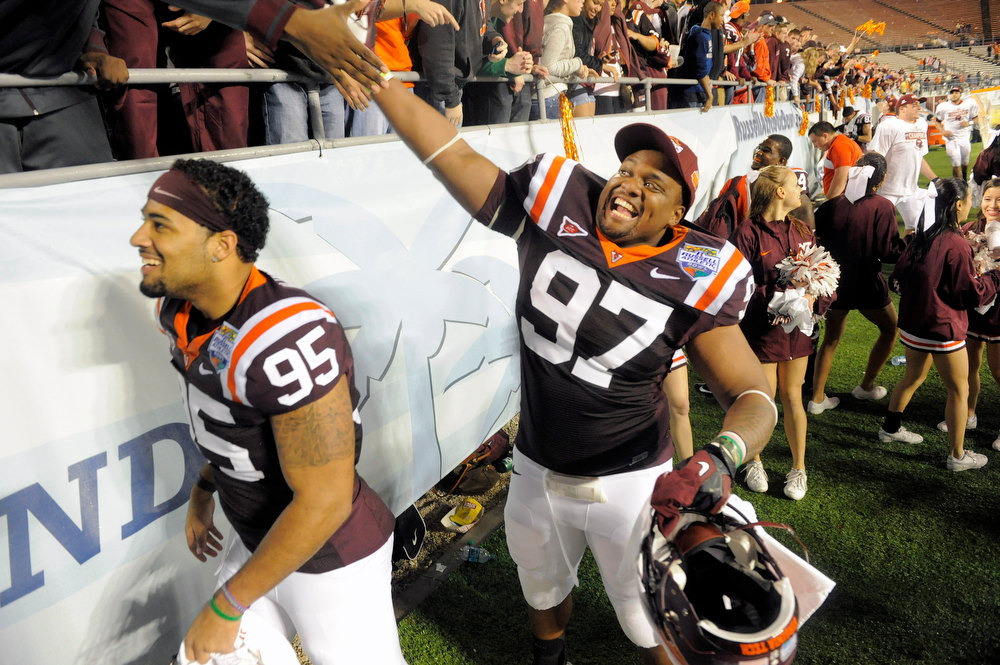 Description of . Virginia Tech defensives tackle Zack McCray, left, and Kris Harley, right, celebrate with fans following their 13-10 win in overtime of an NCAA college football Russell Athletic Bowl game against Rutgers, Friday, Dec. 28, 2012, in Orlando, Fla. (AP Photo/Brian Blanco)