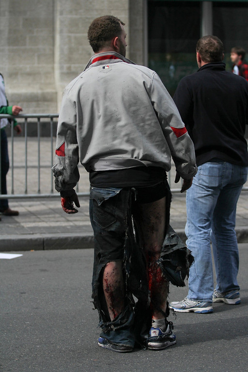 . An injured man stands at the scene of an explosion at the Boston Marathon in Boston, Massachusetts, April 15, 2013. Two explosions struck the marathon as runners crossed the finish line on Monday, witnesses said, injuring an unknown number of people on what is ordinarily a festive day in the city. REUTERS/Daily Free Press/Kenshin Okubo/Boston University/Handout