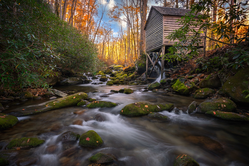Water mill next to stream in autumn