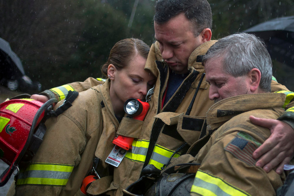 Description of . Sandy Hook Village firefighters observe a moment of silence near Sandy Hook Elementary in Newtown, Connecticut December 21, 2012. Many Americans remembered the victims of the Newtown, Connecticut, school massacre with a moment of silence on Friday, as a powerful U.S. gun rights lobbying group prepared to plunge into the national debate over gun control.  REUTERS/Adrees Latif