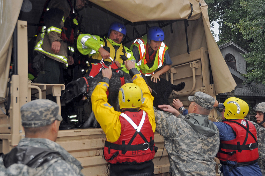. In this photo provided by the Colorado National Guard,  Colorado National Guardsmen place a dog into a high-clearance military vehicle as they rescue people and pets stranded by flooding in Lyons, Colo., Thursday, Sept. 12, 2013. Thousands more people in Colorado were ordered to evacuate Friday, Sept. 13, as water rose to dangerous levels amid a storm system that has been dropping rain for a week. Rescuers struggled to reach dozens of people cut off by flooding in mountain communities. (AP Photo/Army National Guard, Sgt. Joseph K. VonNida)