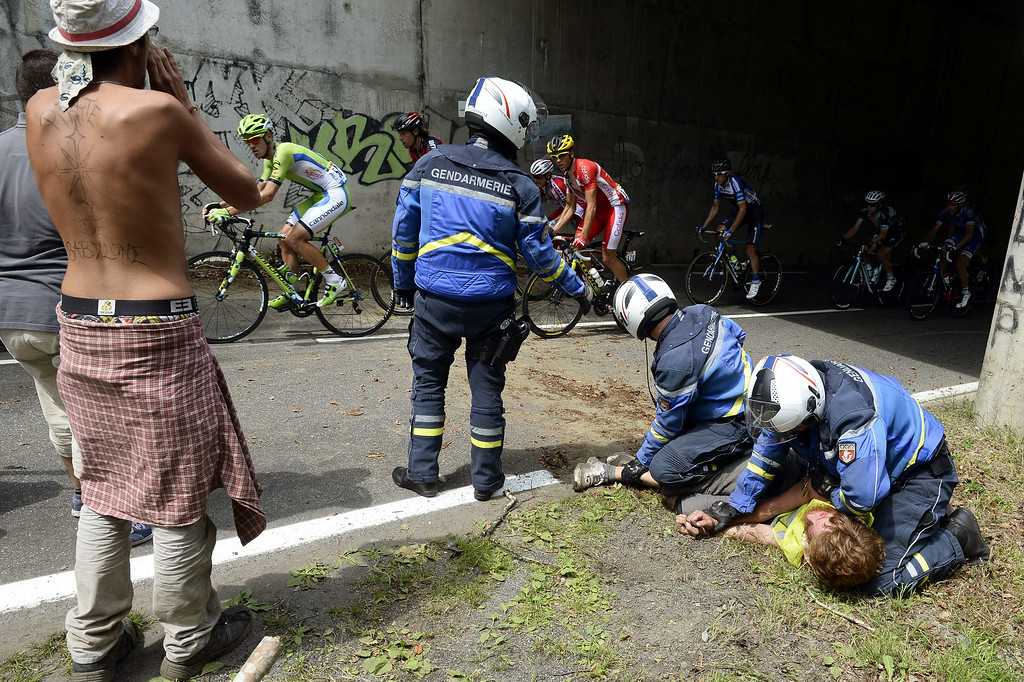 . French gendarmes arrest a man demonstrating against the Tour de France, as the pack rides past during the 145.5 km eighteenth stage of the 101st edition of the Tour de France cycling race on July 24, 2014 between Pau and Hautacam, southwestern France.  AFP PHOTO / LIONEL  BONAVENTURE/AFP/Getty Images