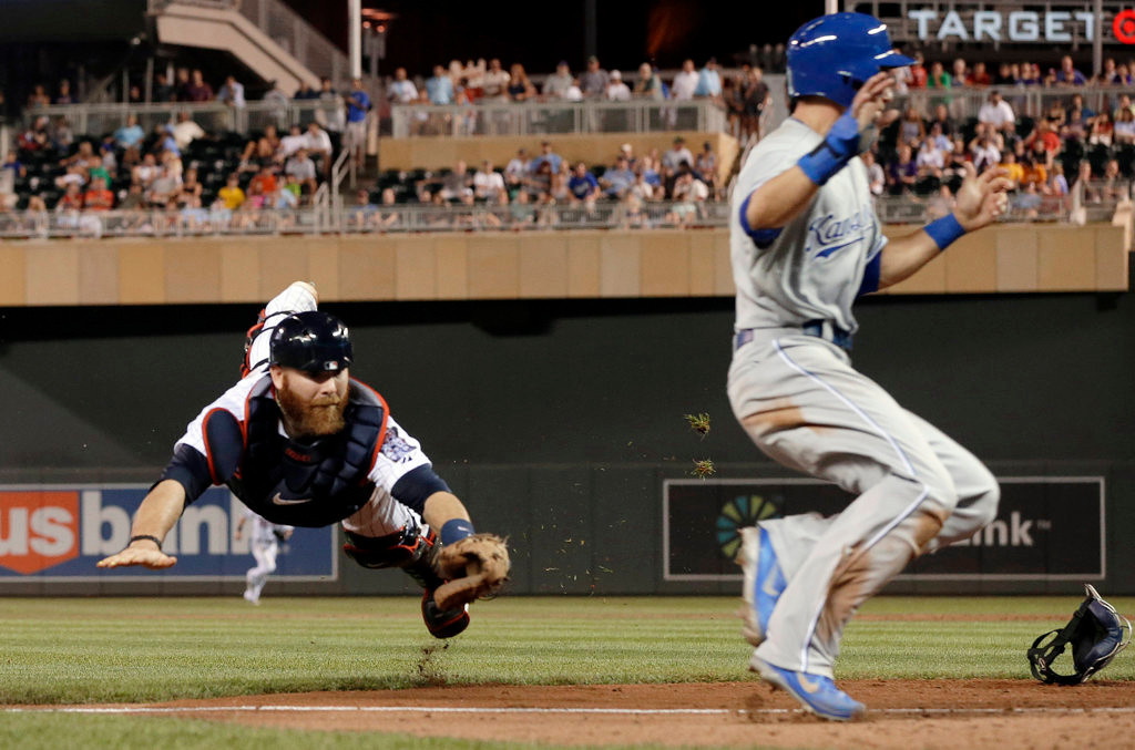. Minnesota Twins catcher Ryan Doumit, left, makes a futile dive as Kansas City Royals\' David Lough runs by to score on a bunt single by Jarrod Dyson in the eighth inning of a baseball game. (AP Photo/Jim Mone)