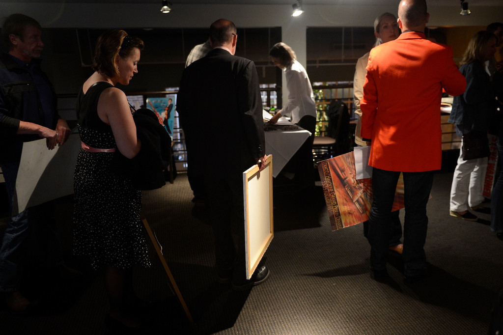 . DENVER, CO. - APRIL 30:  Bid winners wait to pay for their art work after an auction at Strings Restaurant after the last day of service as the Denver favorite closes April 30, 2013 Denver, Colorado. (Photo By Joe Amon/The Denver Post)