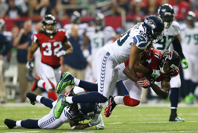 . Julio Jones #11 of the Atlanta Falcons is tackled by  K.J. Wright #50 and  Richard Sherman #25 of the Seattle Seahawks in the third quarter of the NFC Divisional Playoff Game at Georgia Dome on January 13, 2013 in Atlanta, Georgia.  (Photo by Mike Ehrmann/Getty Images)