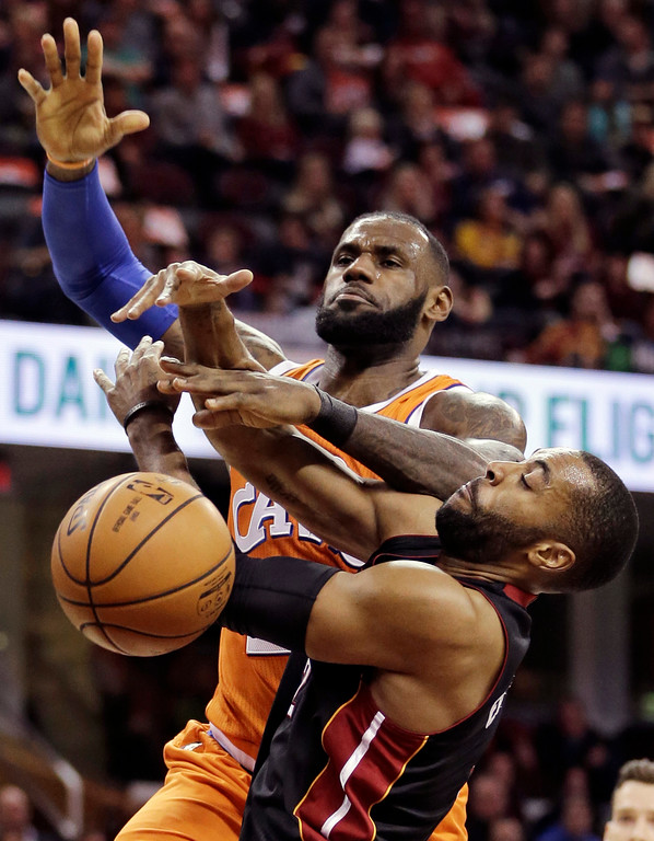 . Cleveland Cavaliers\' LeBron James, top, is fouled by Miami Heat\'s Wayne Ellington in the first half of an NBA basketball game Friday, Dec. 9, 2016, in Cleveland. (AP Photo/Tony Dejak)