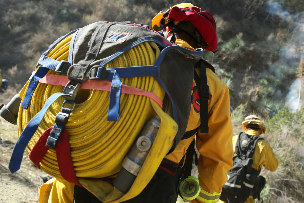 . A Cal Fire crew carries a fire line on his back at a flare-up of the Colby Fire burning for a second day in the hillside above Highway 39 on January 17, 2014 in Azusa, California. The so-called Colby Fire, has burned about 1,700 acres in the Angeles National Forest north of Glendora and Azusa. (Photo by Jonathan Alcorn/Getty Images)