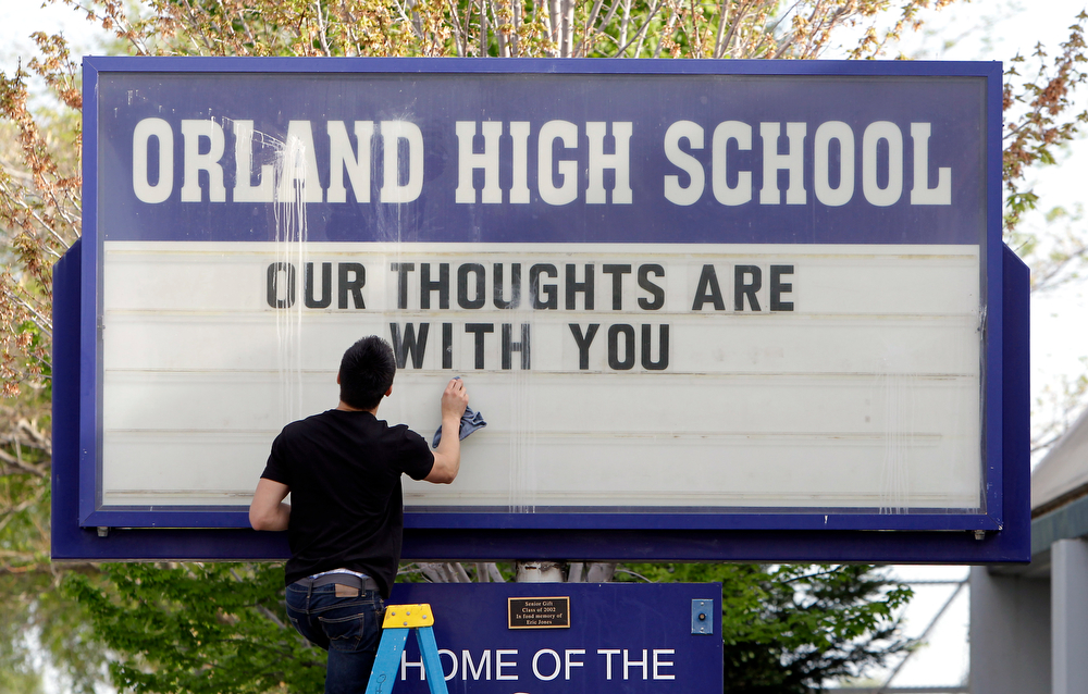 Description of . Sergio Parra, 16, a 10th grader at Orland High School, cleans the glass on the school's sign, Friday, April 11, 2014, after placing a memorial remembering the victims of a fiery crash between a tour bus and a FedEx truck in Orland, Calif.  Ten people were killed and dozens injured in the fiery crash that happened Thursday, between the truck and a bus carrying high school students on a visit to a Northern California college.  Orland High is across the street from where a Red Cross shelter was setup to handle some of survivors of the accident. (AP Photo/Rich Pedroncelli)