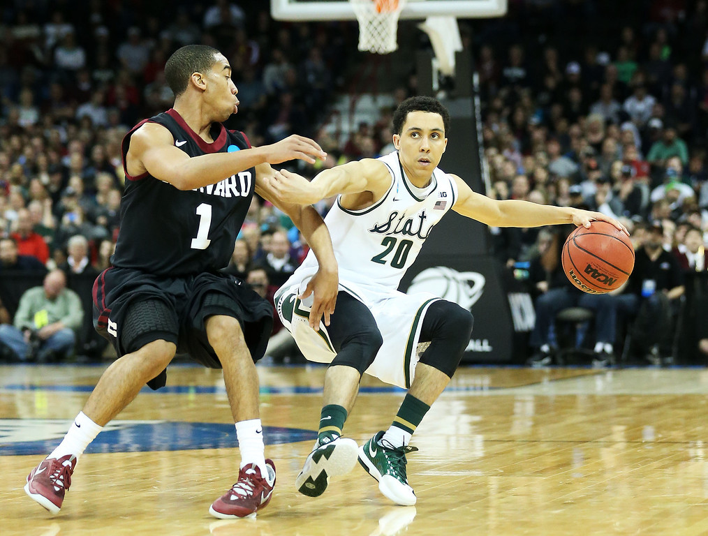 . SPOKANE, WA - MARCH 22:  Travis Trice #20 of the Michigan State Spartans drives against Siyani Chambers #1 of the Harvard Crimson in the second half during the Third Round of the 2014 NCAA Basketball Tournament at Spokane Veterans Memorial Arena on March 22, 2014 in Spokane, Washington.  (Photo by Stephen Dunn/Getty Images)