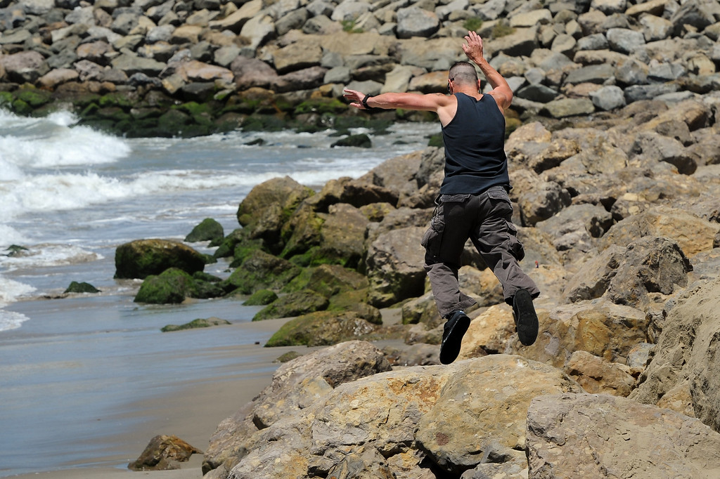 . A man jumps from boulder to boulder at Hueneme Beach where sand has washed away during the past several months, Monday, July 15, 2013. (Michael Owen Baker/L.A. Daily News)