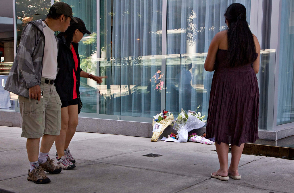 ". Passersby pause at a small memorial for Canadian actor Cory Monteith outside a downtown hotel in Vancouver, British Columbia July 14, 2013. Monteith, 31-year-old heartthrob of Fox\'s musical comedy television series ""Glee\"", was found dead on Saturday in his Vancouver hotel room, police said. Police and paramedics found no signs of foul play and the cause of death was not clear. REUTERS/Andy Clark"