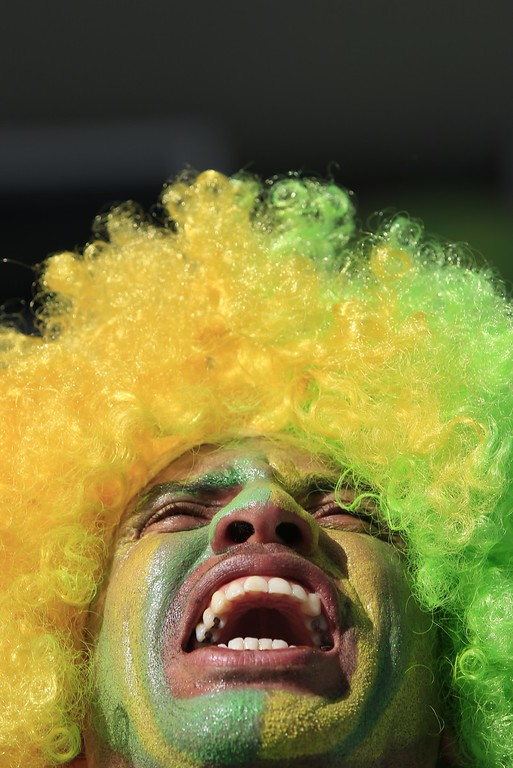 . A Brazilian fan cheers prior to the Group A football match between Brazil and Croatia at the Corinthians Arena in Sao Paulo during the 2014 FIFA World Cup on June 12, 2014.  AFP PHOTO / ADRIAN DENNIS/AFP/Getty Images