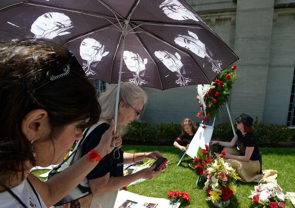 . (l-r) Angella Wains, from Rio de Janeiro, and Silvily Thomas, from Germany, take photos while shaded by a Michael Jackson umbrella. Shirley Alves, from Montreal, and Susan Bryant from Los Angeles, decorate a wreath. Michael Jackson impersonators, and fans gathered at the Great Mausoleum at Forest Lawn Memorial Park in Glendale to honor Jackson on the 5th anniversary of his death.  Glendale, CA. 6/25/2014 (Photo by John McCoy Daily News)