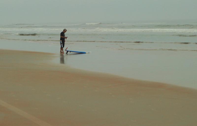 A lone surfer was preparing to enter the ocean at a beach near Ormond Beach, FL.