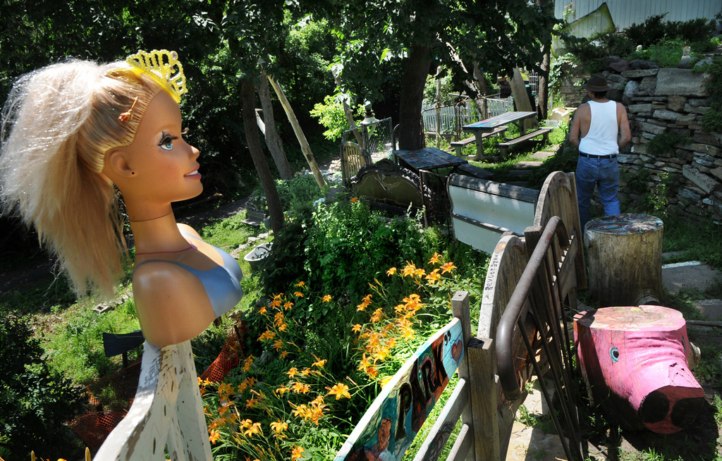 """. Arjo Adams said he came out one morning and someone had put up the doll\'s head in the \""""People\'s Park\"""" and that a girl came out with two young kids and painted the pig stool. Arjo Adams\' house and \""""People\'s Park\"""" --  the  next-door folk-art sculpture garden have been condemned.  The city-owned lot next to his home has been transferred to St. Paul Parks and Recreation, which plans to use the lot as a buffer to a bike path and the East Side Heritage Park. (Pioneer Press: Jean Pieri)"""