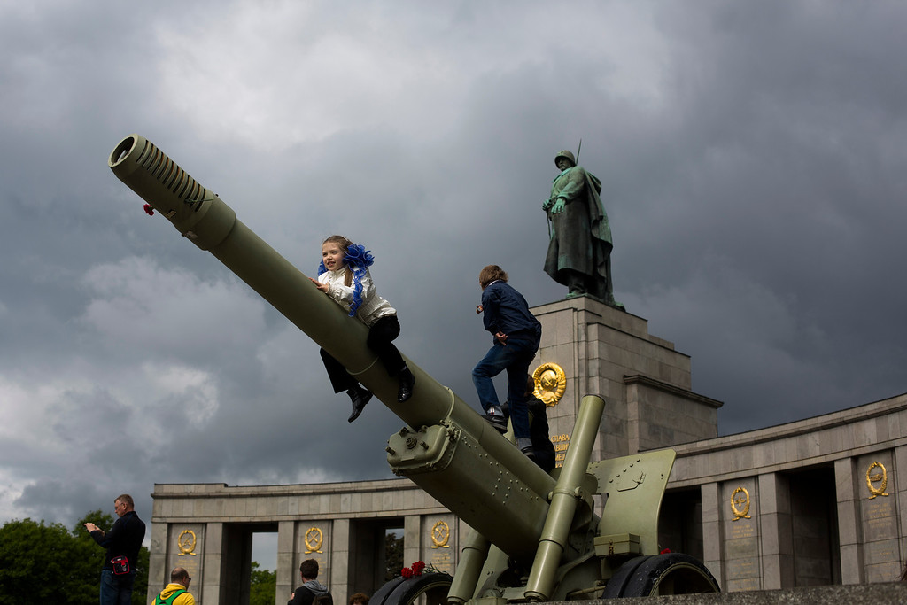 . Russian girl Sophia plays with other children on an ordnance during the celebrations of Victory Day at the Soviet war monument and cemetery at the district Tiergarten in Berlin, Germany, Friday, May 9, 2014.  Hundreds of Russians attend the celebration in the German capital to mark the victory over Nazi-Germany. (AP Photo/Markus Schreiber)