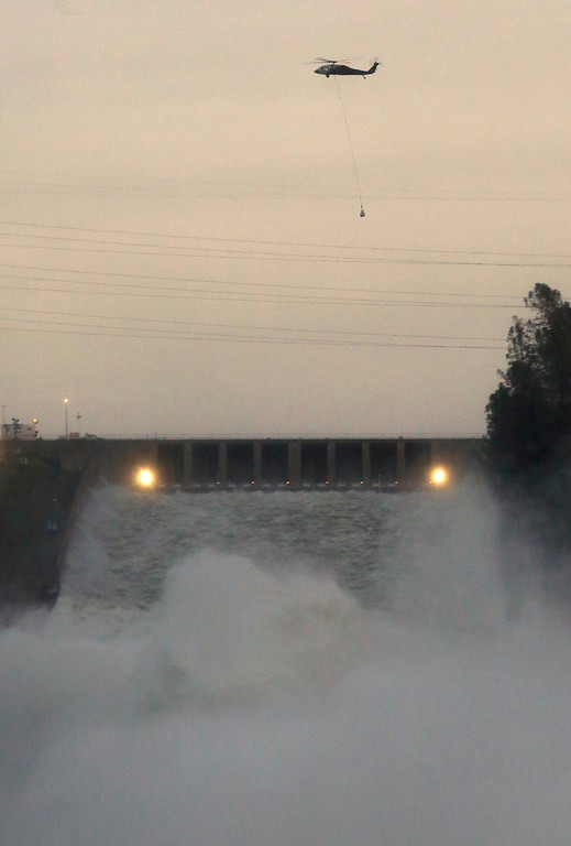 . A helicopter flies over Oroville Dam\'s main spillway to drop a bag of rocks that will be placed on a hole on the lip of the emergency spillway Monday, Feb. 13, 2017, in Oroville, Calif. The barrier, at the nation\'s tallest dam, is being repaired a day after authorities ordered mass evacuations for everyone living below the lake out of concerns the spillway could fail and send a 30-foot wall of water roaring downstream. (AP Photo/Rich Pedroncelli)