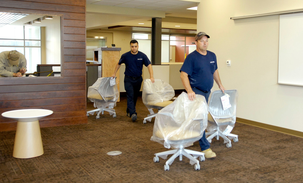 . Mark Dzomba and Israel Rodriguez, left, of Ohio Desk move office furniture into one of the classrooms at the new Holden University Center in September 2011. (News-Herald file)