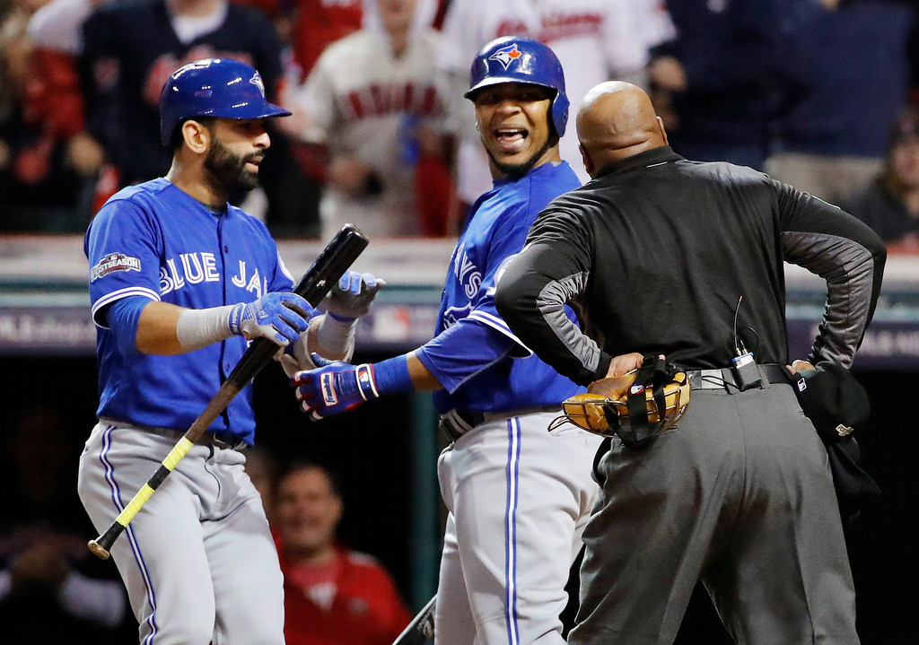 . Toronto Blue Jays\' Jose Bautista, left, listens as Edwin Encarnacion, center, and home plate umpire Laz Diaz exchange words after Encarnacion was called out on strikes during the eighth inning in Game 1 of baseball\'s American League Championship Series against the Cleveland Indians in Cleveland, Friday, Oct. 14, 2016. (AP Photo/Matt Slocum)