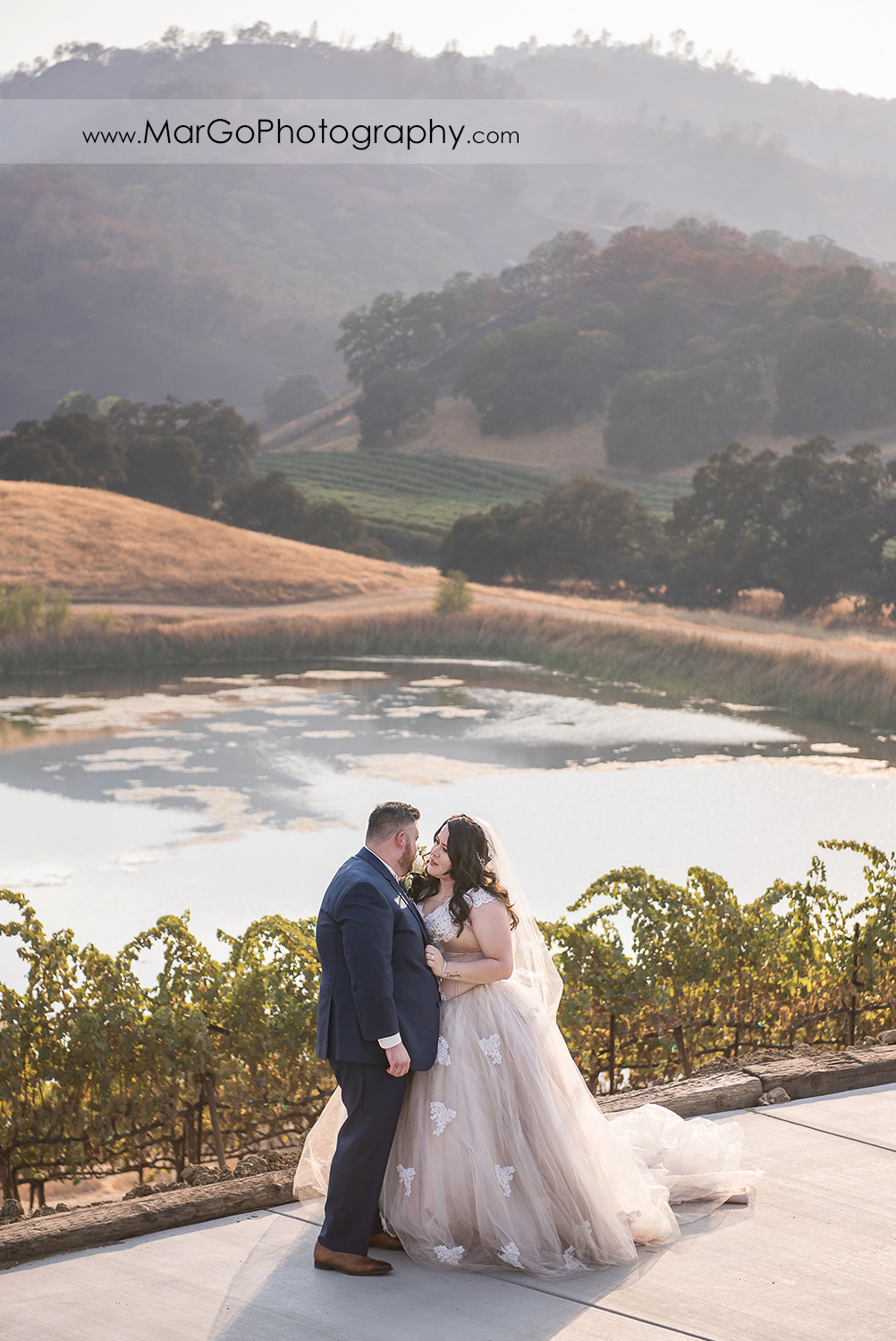 bride and groom looking at each other with pond and hills view in background at Taber Ranch Vineyards