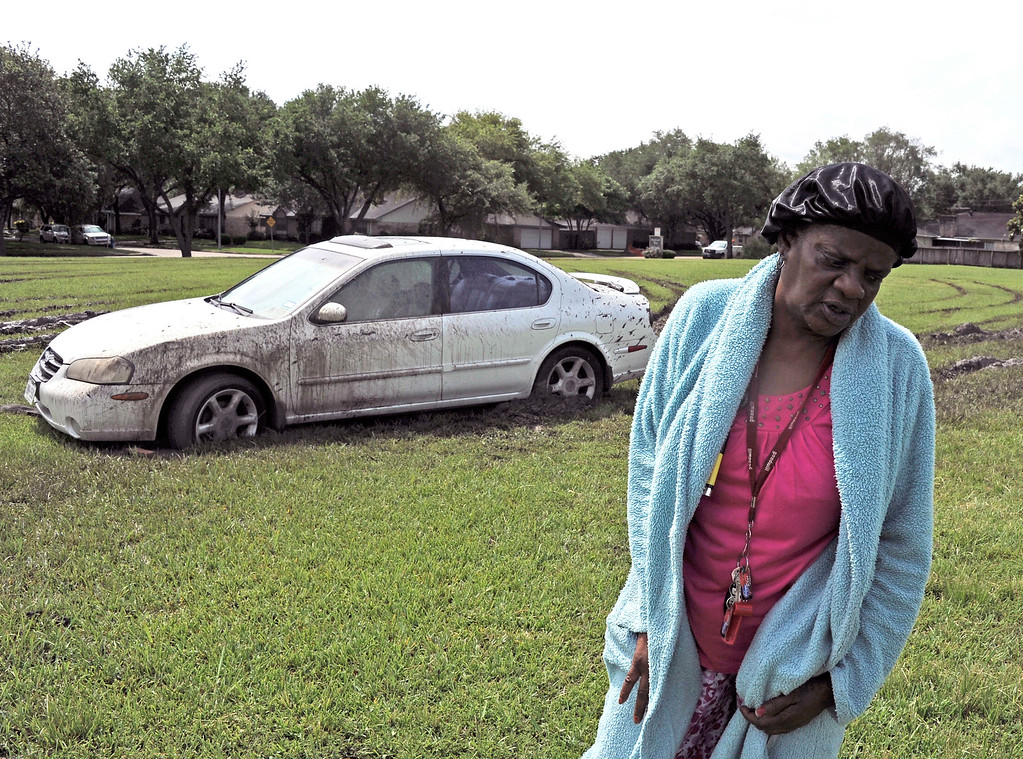 . Lorraine Joseph talks about her car still stuck the mud despite several attempts to pull it out Wednesday, May 27, 2015, in Houston. Each attempt failed when the rescuers also got stuck in the mud. The death toll from a barrage of storms and floods in Texas and Oklahoma climbed to at least 19 on Wednesday, with over a dozen people missing, and another round of rain threatened to complicate the cleanup in hard-hit Houston.  (AP Photo/Pat Sullivan)