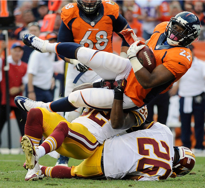 . Denver Broncos running back C.J. Anderson fights for extra yardage against the Washington Redskins in the fourth quarter at Sports Authority Field. (Photo by Steve Nehf/The Denver Post)