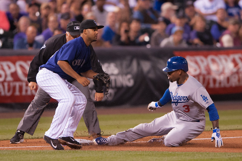 . Carl Crawford #3 of the Los Angeles Dodgers slides into third base on his fourth-inning triple as Rafael Ynoa #43 of the Colorado Rockies awaits the throw during a game at Coors Field on September 15, 2014 in Denver, Colorado.  (Photo by Dustin Bradford/Getty Images)