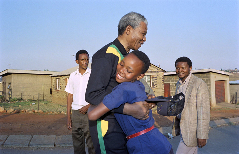 . Anti-apartheid leader and African National Congress (ANC) member Nelson Mandela hugs, October 1990, a young Sowetan girl as he visits the black township near Johannesburg. (Photo credit should read ALEXANDER JOE/AFP/Getty Images)