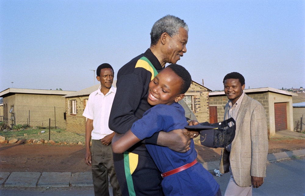 Description of . Anti-apartheid leader and African National Congress (ANC) member Nelson Mandela hugs, October 1990, a young Sowetan girl as he visits the black township near Johannesburg. (Photo credit should read ALEXANDER JOE/AFP/Getty Images)