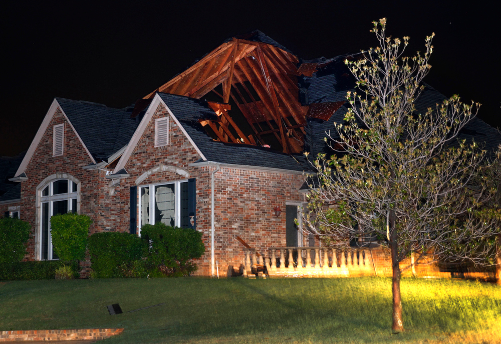 . A large hole was blown out of the roof of a home on Lakeshore Dr. outside of Cleburne, after a tornado Wednesday night, May 15, 2013. The top of the roof was still intact leaving a large hole through the roof of Lake Pat Cleburne home. Cleburne Mayor Scott Cain early Thursday declared a local disaster as schools canceled classes amid the destruction. (AP Photo/The Dallas Morning News, Tom Fox)
