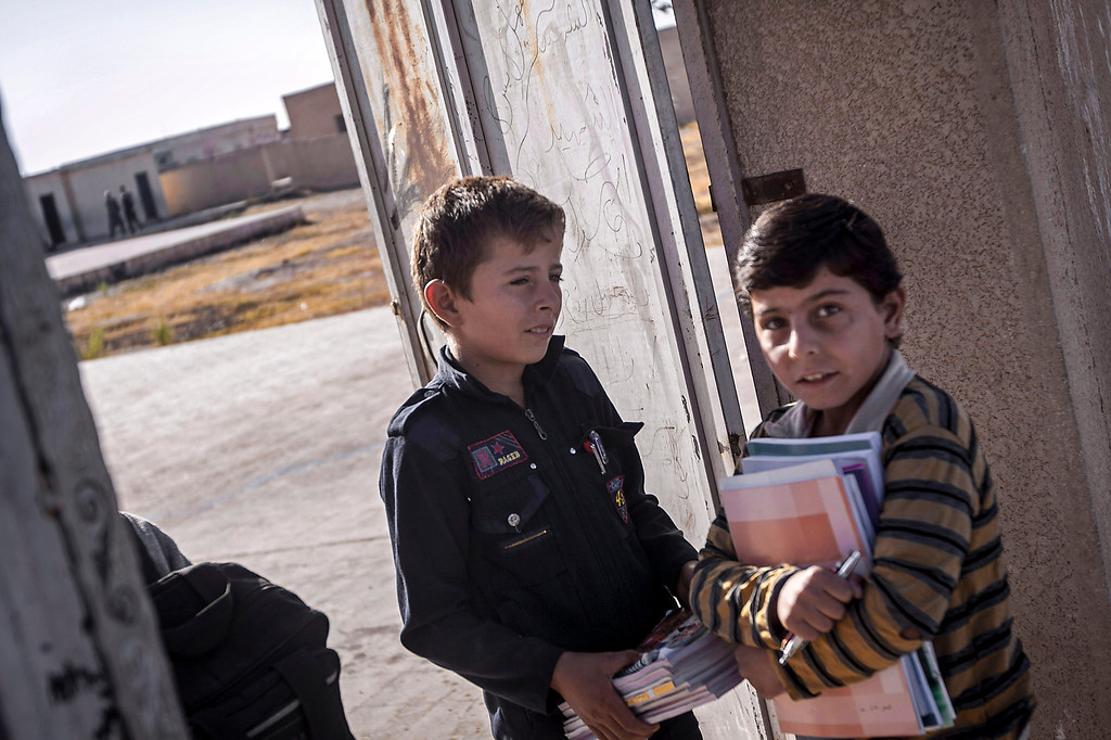 . In this Thursday, Sept. 26, 2013 photo, 12-year-old Abdo al-Fikri, left, arrives to school in Madaya village as classes begin in the Idlib province countryside of Syria. It has been a year since al-Fikri and his siblings were last in school. The area has seen ongoing battles between opposition forces and troops loyal to President Bashar Assad, and like pretty much everything else in Madaya, the school was forced to shut down because of the violence. (AP Photo)