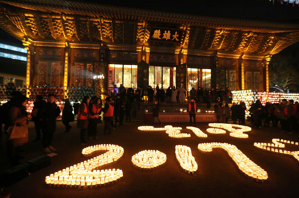 . Buddhists light candles during New Year celebrations at Jogye Buddhist temple in Seoul, South Korea, early Sunday, Jan. 1, 2017. (AP Photo/Ahn Young-joon).