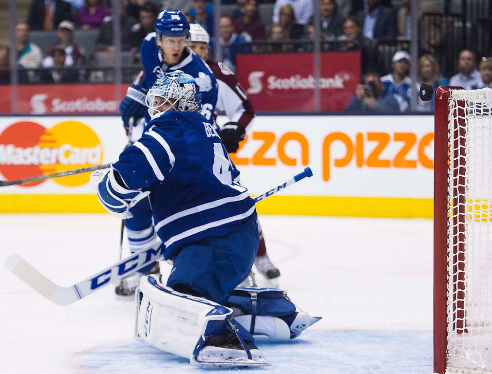 . Toronto Maple Leafs goalie Jonathan Bernier looks back as the puck rings off the crossbar on a Colorado Avalanche shot during the first period of an NHL hockey game in Toronto on Tuesday, Oct. 8, 2013. (AP Photo/The Canadian Press, Nathan Denette)
