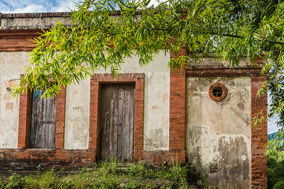 Brick and concrete structure along the road with old wooden doors