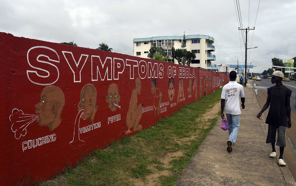 . People walk past a wall bearing information about the symptoms of Ebola in Monrovia on September 25, 2014. World leaders were asked to pledge urgently needed aid to battle Ebola in West Africa as Sierra Leone quarantined one million people in a desperate bid to beat back the deadly virus. US President Barack Obama warned that not enough was being done to tackle the crisis that has left close to 3,000 dead and is spreading at an alarming pace. PASCAL GUYOT/AFP/Getty Images