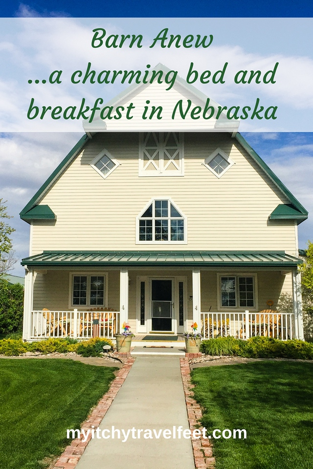 Text on photo: Barn Anew...a charming bed and breakfast in Nebraska. Photo: yellow barn with dark green trim, shaded front porch and sidewalk leading up to the barn.