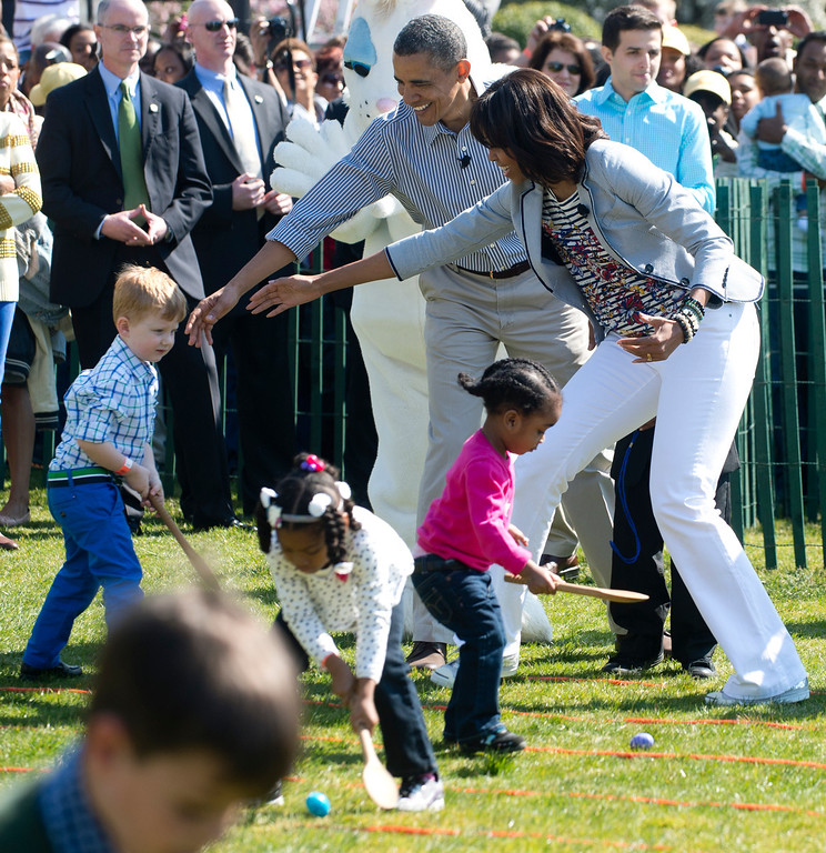 . US President Barack Obama (C) and First Lady Michelle Obama (R) cheer on children as they race to roll eggs as they participate in the White House Easter Egg Roll on the South Lawn of the White House in Washington, DC, April 1, 2013. Obama hosts the annual event, featuring live music, sports courts, cooking stations, storytelling and Easter egg rolling. AFP PHOTO / Saul LOEB/AFP/Getty Images