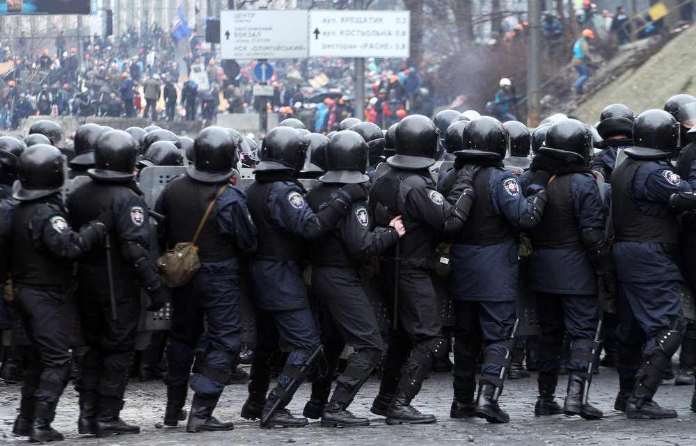 . Riot police face anti-government protesters during clashes central Kiev on February 20, 2014. Ukraine\'s brittle truce shattered on February 20 in fierce clashes between baton-wielding protesters and riot police that claimed at least 27 lives just as EU envoys were holding crisis talks with the embattled president. Bodies of anti-government demonstrators lay amid smouldering debris after masked protesters hurling Molotov cocktails and stones forced gun-toting police from Kiev\'s iconic Independence Square -- the epicentre of the ex-Soviet country\'s three-month-old crisis.   SERGEY GAPON/AFP/Getty Images