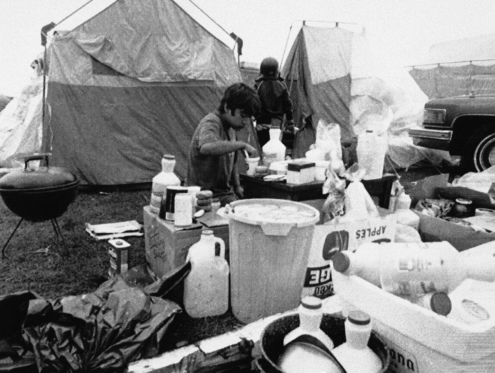 . Juanito Garcia, center, whose home was severely damaged by the earthquake, eats outside the temporary quarters of his family, Saturday, Oct. 21, 1989, Watsonville, Calif. Hundreds of the areas residents were forced to move into tent shelters following the quake. (AP Photo/Bob Galbraith)